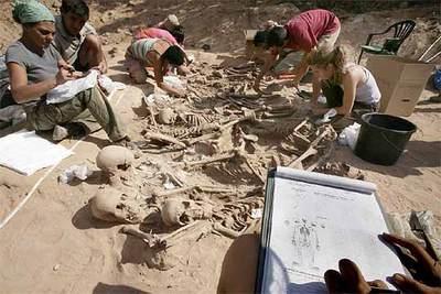 Un equipo de antropólogos y arqueólogos limpia los esqueletos de la fosa de La Andaya (Lerma) antes de trasladarlos al laboratorio. / Foto: Mabel García. El País